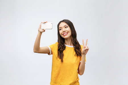Image of excited happy young woman isolated over grey background make selfie by camera. Stockfoto