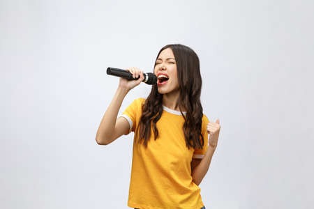 beautiful stylish woman singing karaoke isolated over white background. Standard-Bild