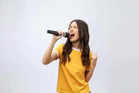 beautiful stylish woman singing karaoke isolated over white background. Foto de archivo