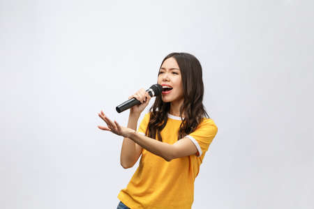 schöne stilvolle Frau singt Karaoke auf weißem Hintergrund.