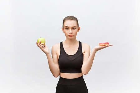 8fa40a750e868 Young woman choosing between donut and apple on white background. Diet food  concept Stock Photo