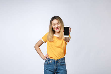Close up portrait of a smiling asian woman showing blank screen mobile phone while standing isolated over gray background.