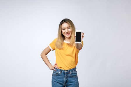 Primo piano ritratto di una donna asiatica sorridente che mostra il telefono cellulare a schermo vuoto mentre si trova isolato su uno sfondo grigio.