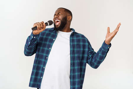 Portrait of cheerful positive chic handsome african man holding microphone singing song. Isolated on white background. Foto de archivo