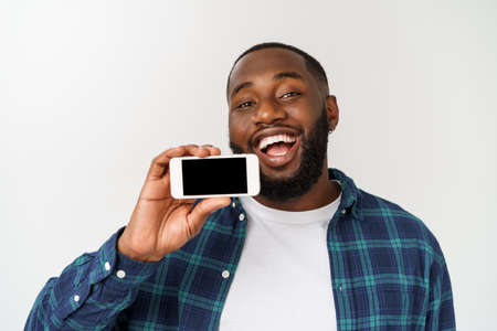 Handsome african guy isolated on grey background, presenting smart phone and pointing with finger at blank black screen.