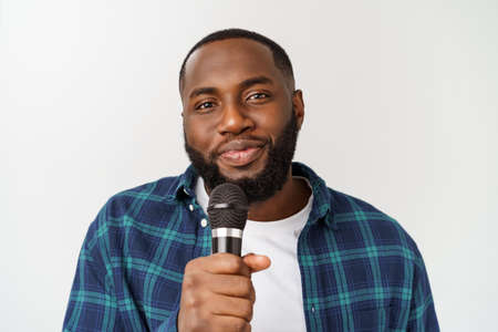 young handsome african american boy singing emotional with microphone isolated on white background.