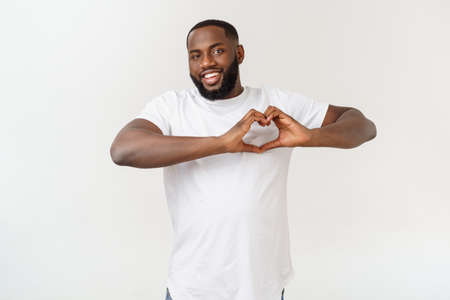 Portrait of happy excited afroamerican bearded man fall in love and gesture heart with fingers.