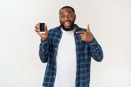 Handsome african american man isolated on grey background, presenting smart phone.