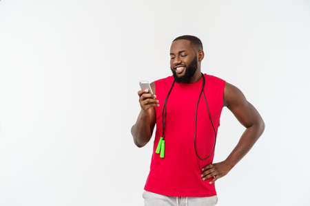 Mature fit African American man texting on mobile and holding elastic rope.