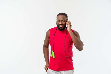 Dojrzały mężczyzna Afroamerykanin pasuje do telefonu komórkowego i przytrzymanie elastycznej liny.