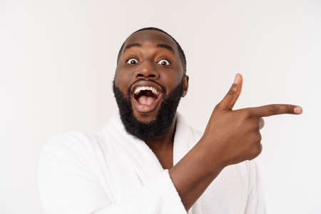 Black guy wearing a bathrobe pointing finger with surprise and happy emotion. Isolated over whtie background. Stock Photo