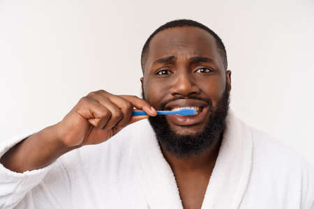 portrait of a happy young dark-anm brushing his teeth with black toothpaste on a white background. Stock Photo