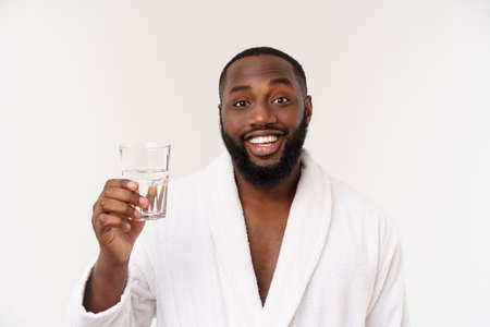 Thirsty young african man holding glass drinking water for body health isolated on white studio background.