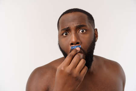 Close up of a happy naked african man shaving with razor isolated over gray background