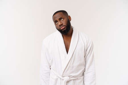 Young african american man wearing bathrobe over isolated white background thinking looking tired and bored with depression problems.