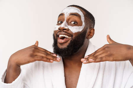 Young african-american guy applying face cream on white background. Portrait of a young happy smiling african man at studio. High fashion male model.