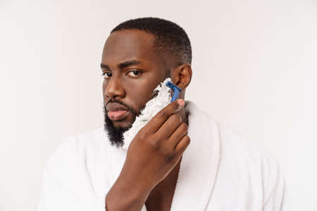African American man smears shaving cream on face by shaving brush. Male hygiene. Isolated on white background. Studio portrait