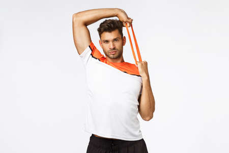 Handsome muscular sexy young sportsman in sports t-shirt, hold hands over head and stretching resistance band with carefree, unbothered expression, showing strengths, bragging how strong his muscles