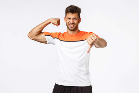 Handsome fit and muscular man dont like his body shape, show thumb down as raise one hand with biceps, grimacing disappointed, frowning upset, workout hard in gym, standing white background Stock Photo