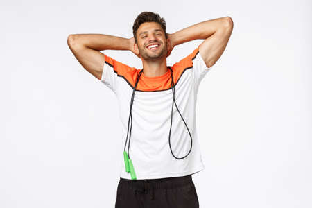 Sexy good-looking athletic male, holding hands behind head carefree pose, smiling satisfied and proud, bit record on skipping rope, finish workout, fitness, pleased with good training session Stock Photo