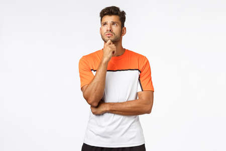 Concerned, worried young handsome male athlete in activewear, rub chin and look up anxious, thinking, cant make decision, make-up mind, standing thoughtful and upset over white background