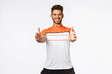 Handsome cheerful young sportsman, fitness instructor showing how easy use resistance band during workout, smiling carefree and enthusiastic. male athlete exercise using gym equipment