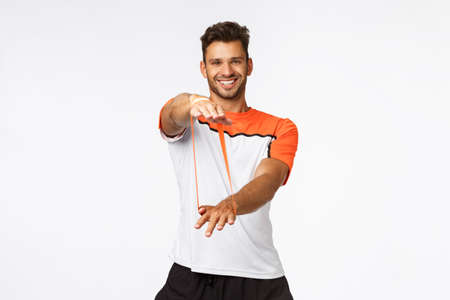 Charismatic male fitness instructor in activewear showing fitness exercises, teach clients how workout with resistance band, stretching with hands and smiling, training and active lifestyle concept