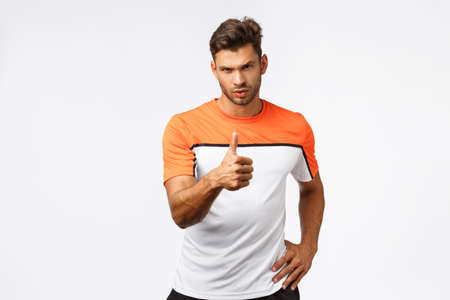 Workout, training and sport concept. Sassy handsome, masculine bearded young man, sportsman showing thumb-up and look camera pleased, satisfied with client doing great, praising you did great Stock Photo