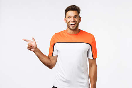 Excited handsome bearded sportsman in sports t-shirt pointing left, see cool equipment in gym, look wondered and amazed, smiling camera astonished, see something awesome. Fitness, lifestyle concept