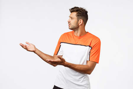 Disappointed sad bearded masculine male trainer in sports t-shirt, looking upset left raising hands in dismay and dislike, judging something bad, expectations failed, standing white background