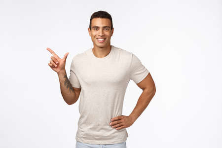 Sports, healthy people and movember concept. Handsome smiling hispanic guy in casual t-shirt, hold hand on waist relaxed, pointing left and grinning satisfied, recommend promo, advertise new product Stock Photo