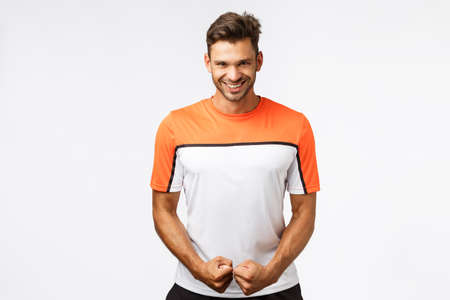 Attractive smiling happy man with bristle, masculine body, smiling assertive and sassy, look satisfied with own strained muscles, feeling powerful and determined, encourage himself before workout