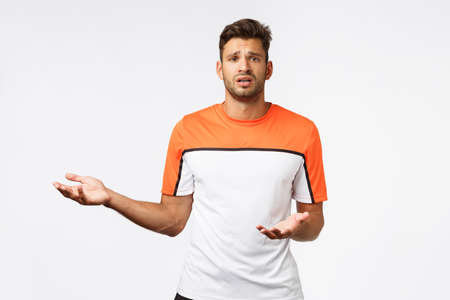 Upset, disappointed gloomy bearded sportsman feeling let down and moody, raising hands in dismay, pointing left, frowning and looking camera, complaining, standing frustrated white background Stock Photo