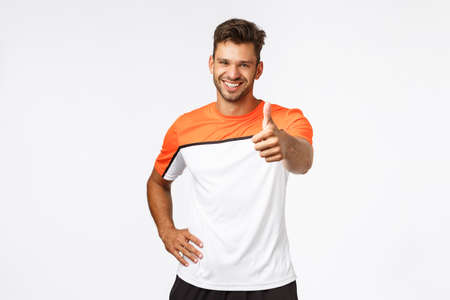 Handsome happy and healthy male athlete, sportsman in good shape showing thumb-up with stretched hand, smiling in approval, fitness trainer encourage client do best during workout in gym Stock Photo