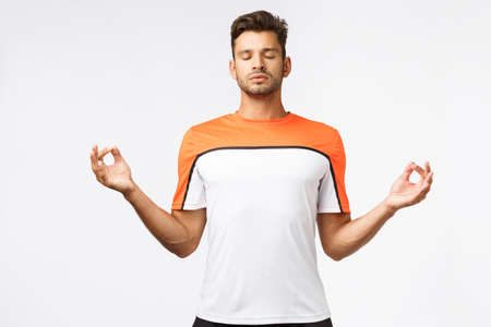 Health, lifestyle and sport concept. Handsome sportsman, raise hands sideways in zen, lotus pose, close eyes and meditating, feeling peaceful, do yoga after workout or before football match