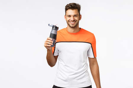 Fitness trainer remind you drink water. Handsome smiling, cheerful sportsman in activewear, finish morning jogging, workout gym practice, grin joyful, holding bottle, standing white background
