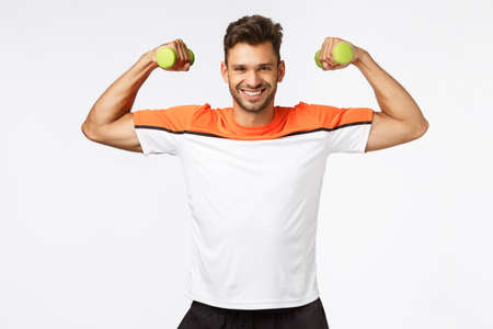 Sport, diet and healthy lifestyle concept. Handsome smiling, happy sportsman enjoy workout, proudly showing his muscles, lift arms and tense biceps to brag perfect body, hold dumbbells at training