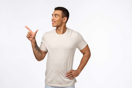 Satisfied and proud, smiling happy hispanic man with short haircut, tattoo, wear casual t-shirt, looking and pointing upper left corner with pleased expression, reading sign, recommend product