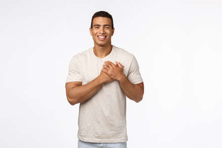 Guy feeling touched and flattered receiving praises. Charming hispanic young man in t-shirt, press hands to heart, smiling and laughing carefree, express gratitude, white background Archivio Fotografico
