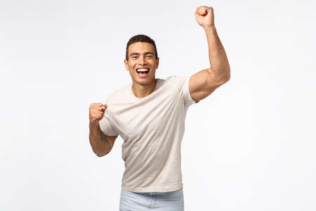 Man lift hand up in hooray motion, cheering for favorite sports team. Handsome young strong guy fist pump and smiling, encourage friend score goal, rooting for someone, placed bet white background Stock fotó