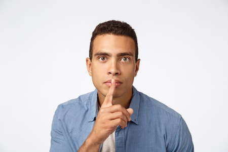 Serious-looking young hispanic man bending towards camera, shushing, make shush or shh sound as press finger to lips, look assertive, ask stay quiet, demand silence, white background