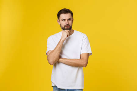 Pensive curious man looking up in thinking pose trying to make choice or decision isolated on yellow background Reklamní fotografie