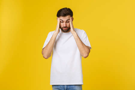 Portrait of young man isolated on yellow background suffering from severe headache, pressing fingers to temples, closing eyes to relieve pain