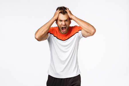 Angry, aggressive mascular sportsman looking furious, grab head in rage and fury, shouting and grimacing from anger and disappointment. Athlete lost match, team scored goal, white background Stock Photo