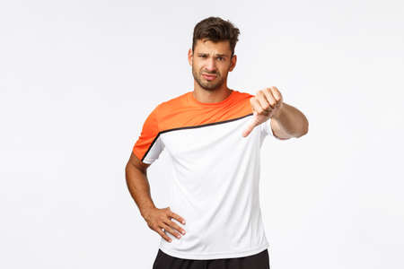 Disappointed handsome sportsman, football player displeased of someone weak attitude, show thumb-down frowning and looking skeptical, judging bad team play during football match, white background