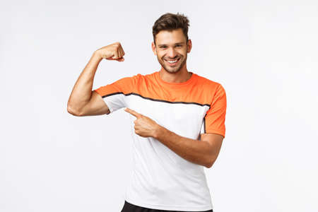 Guy brag with muscles asking if you want touch or gain such good body shape yourself. Sassy smiling, satisfied sportsman show biceps, pointing at arm and grinning, encourage train and workout in gym Stock Photo