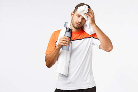 Handsome sportsman wipe sweat from forehead with towel on neck, tilt head and looking tired after good, productive workout, exercise in gym, holding water bottle, drink stop during maraphon