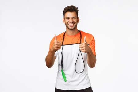 Man praise client efforts, showing thumbs-up supportive in approval or like, wrap skipping rope around neck, smiling satisfied, accept fitness challenge, sportsman like new training in gym Stock Photo