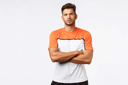 Fitness trainer disappointed client missed training. Handsome strong and masculine man, football player in activewear, sports t-shirt, cross arms over chest, look assertive and determined