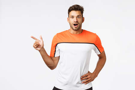 Impressed, surprised good-looking bearded man in sports t-shirt, pointing left, drop jaw and gasping astonished, flushed as discuss impressive goal during foorball match, amazed hear new gym opened Stock Photo